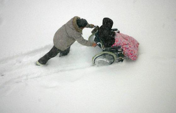 man duwt een persoon in een rolstoel door de sneeuw
