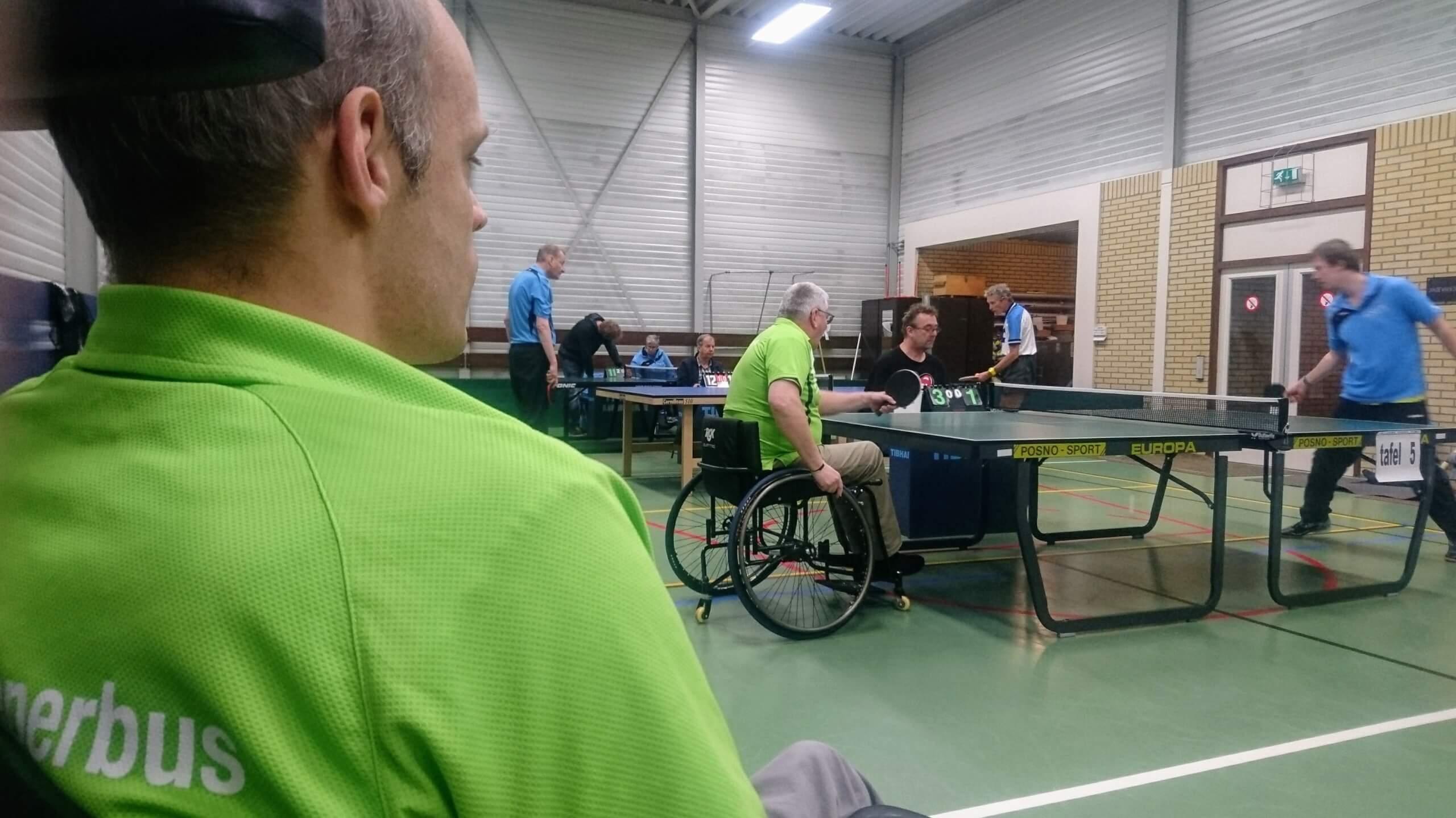 Martijn bekijkt hoe Herman vanuit rolstoel zijn tafeltenniswedstrijd speelt