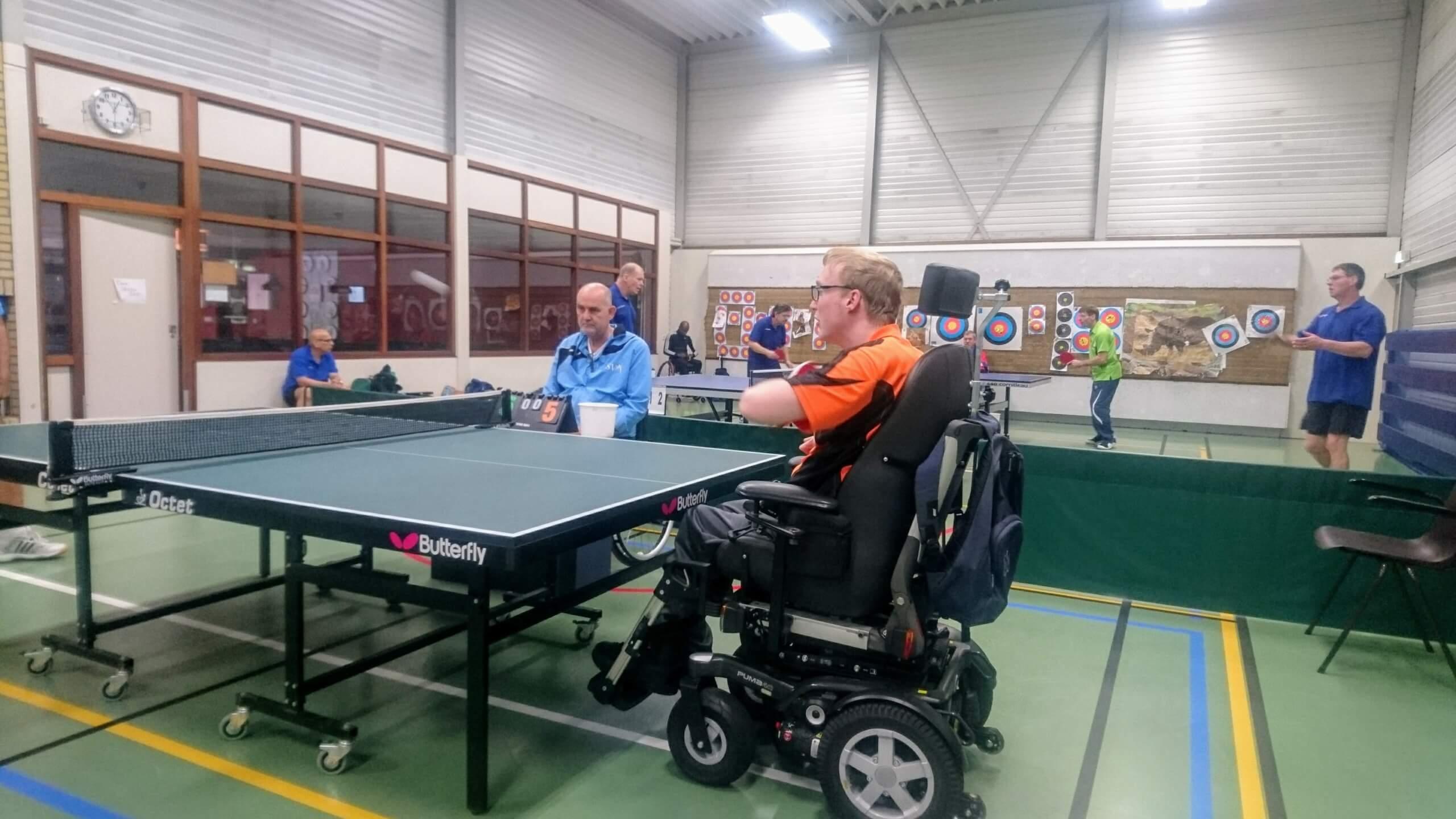 Stefan speelt vanuit zijn elektrische rolstoel tafeltennis. Op achtergrond nog 2 wedstrijden aan de gang met o.a. Hans.