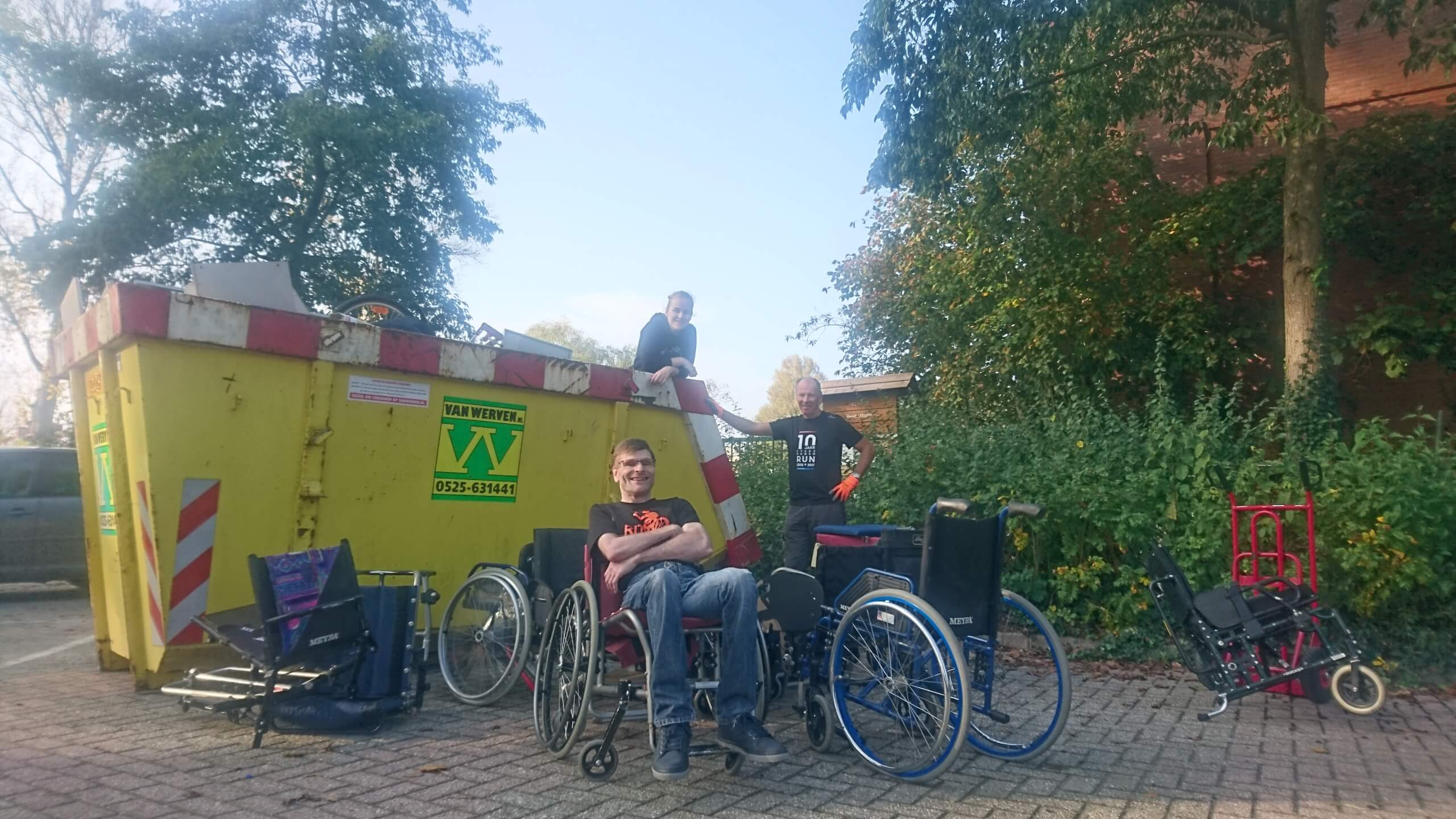 Hans, Talita en Robert poseren voor de container
